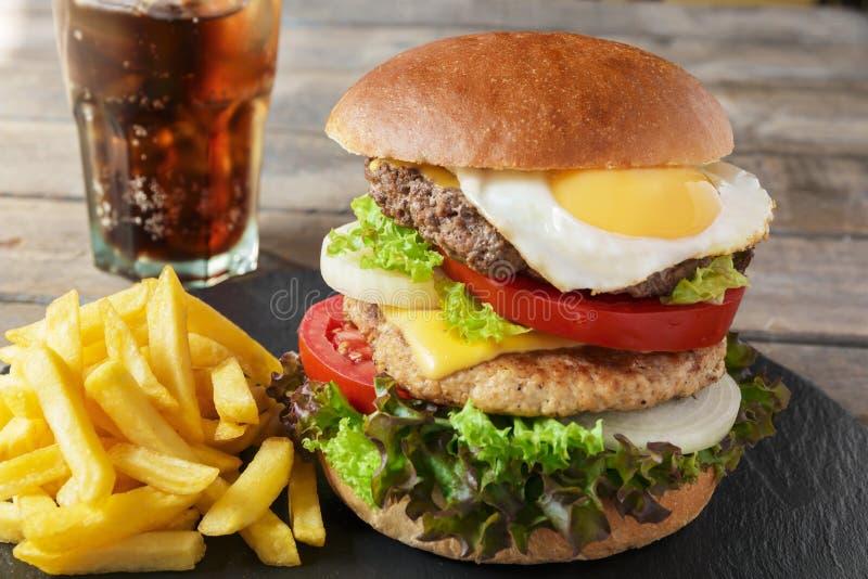 Patate fritte del formaggio dell'uovo della cotoletta della carne dell'hamburger fotografie stock
