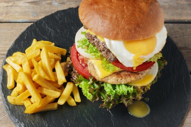 Patate fritte del formaggio dell'uovo della cotoletta della carne dell'hamburger immagine stock