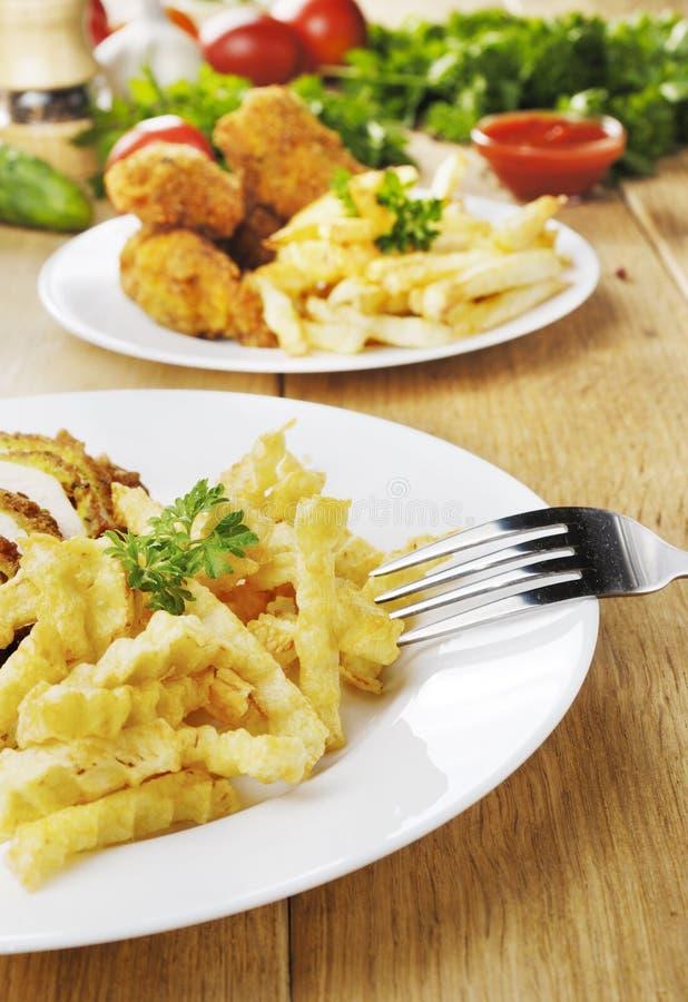 Patate fritte e pollo sul piatto sulla tavola di legno fotografia stock