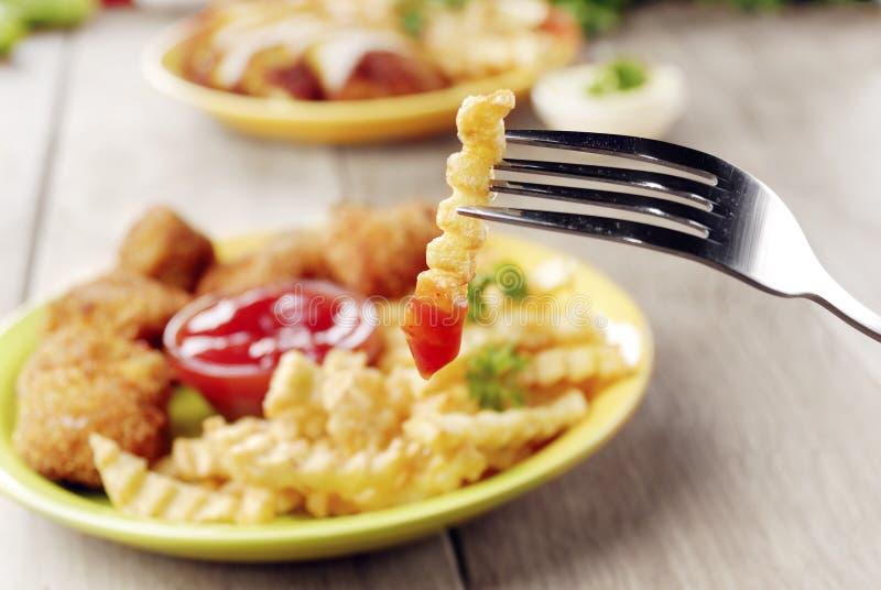 Patate fritte e pollo sul piatto sulla tavola di legno fotografie stock