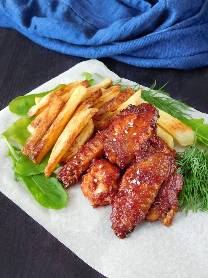 Patate fritte ed ali di pollo arrostite fotografia stock
