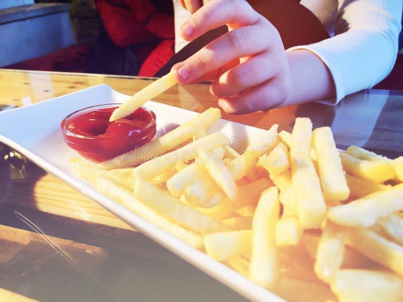 Patate fritte nel piatto bianco con cachup rosso, un pezzo solo della tenuta della ragazza delle patate fritte in sue dita fotografia stock libera da diritti
