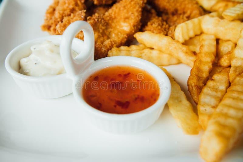 Patate fritte, pepite di pollo e salse su un piatto bianco fotografia stock