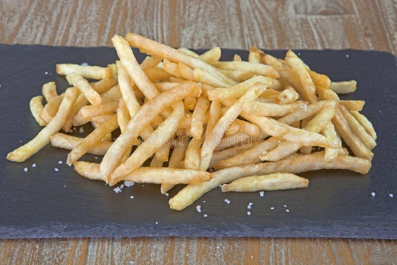 Patate fritte su una pietra nera fotografia stock