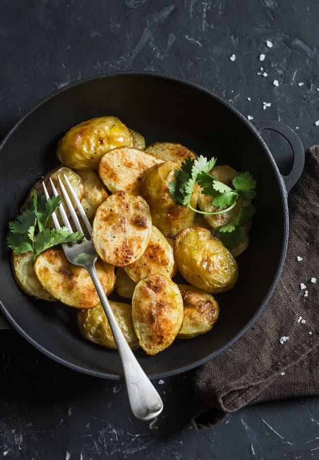 Patate novelle al forno con coriandolo in una padella del ghisa sulla tavola scura, vista superiore Pranzo vegetariano immagine stock libera da diritti