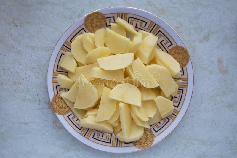 Patate tagliate Nel piatto tagliato della patata Patate crude affettate e sbucciate su un bordo Patate tagliate in una ciotola Pa fotografie stock libere da diritti