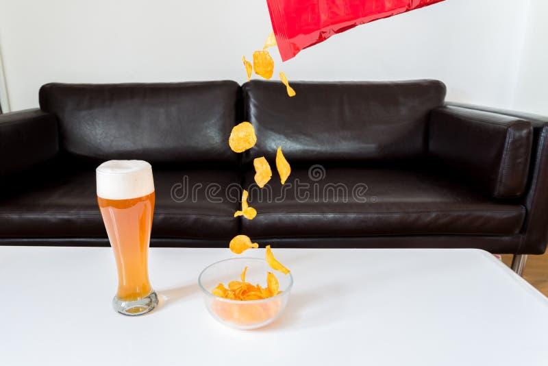 Patatine fritte che cadono da un pacchetto di patatine fritte in una ciotola di vetro con la birra del grano sulla tavola bianca  fotografia stock libera da diritti
