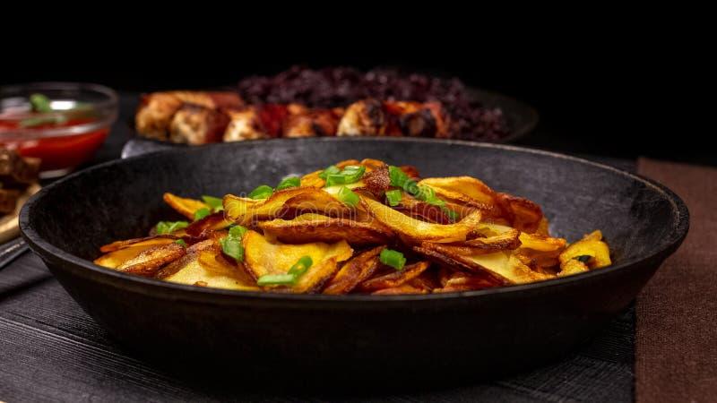 Patatine fritte fritte con i verdi in un vaso, davanti alle salsiccie casalinghe ed al cavolo stufato, su un fondo rustico nero fotografia stock