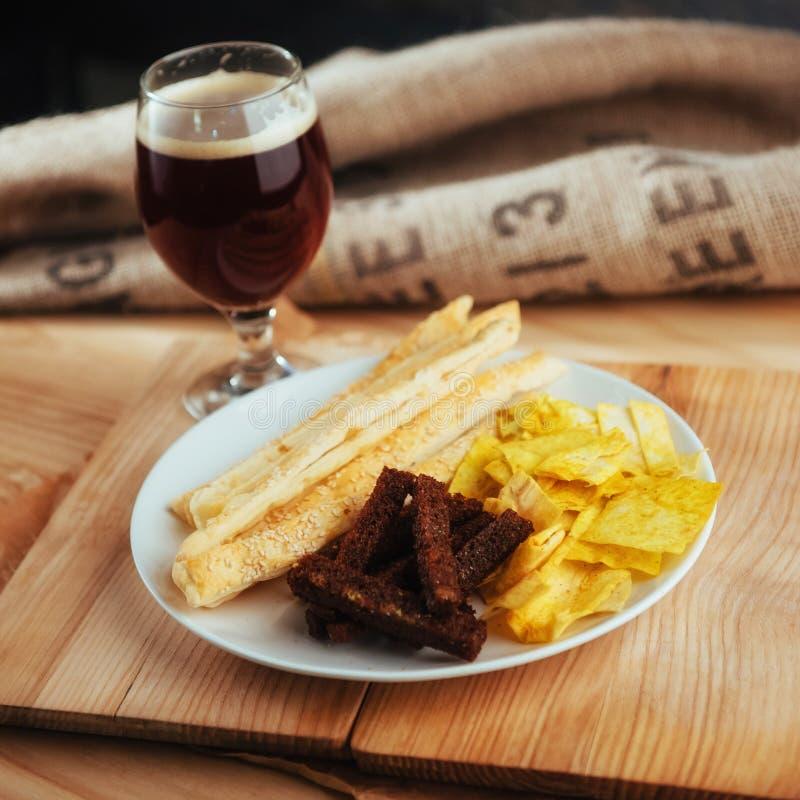 Patatine fritte, cracker croccanti di pane nero con sesamo e bastoni fotografia stock libera da diritti