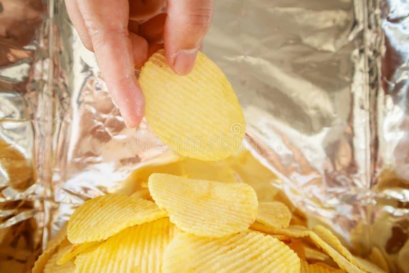 Patatine fritte della tenuta della mano dentro la borsa della stagnola dello spuntino fotografie stock