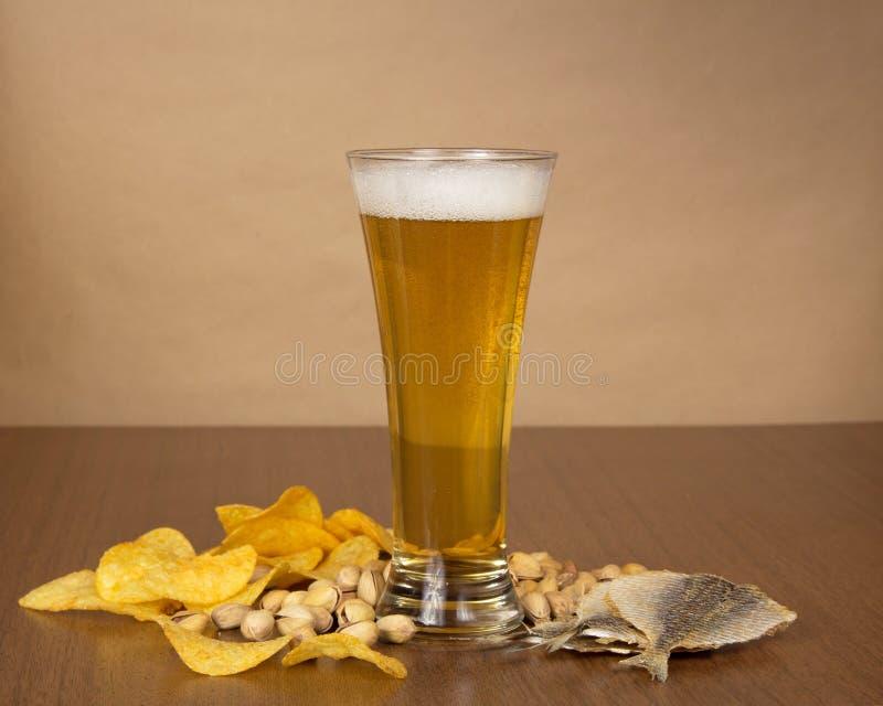 Patatine fritte dorate, pistacchi, pesce salato e birra fotografia stock libera da diritti