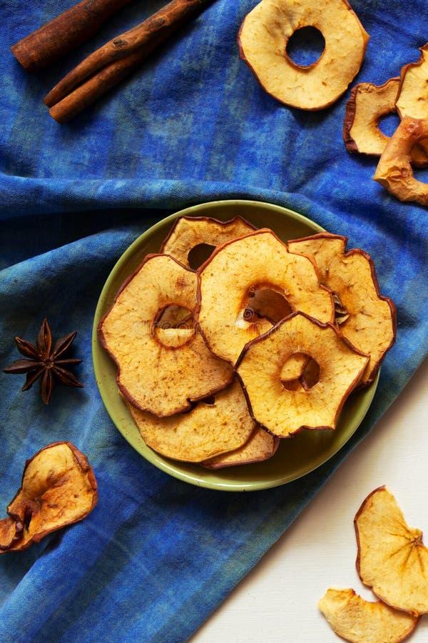 Patatine fritte e cannella di Apple sulla tavola di legno bianca Fette al forno asciutte casalinghe della frutta, spuntino di cad fotografie stock libere da diritti
