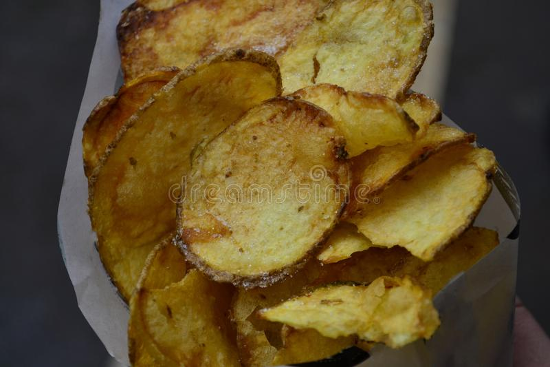 Patatine fritte gialle croccanti rotonde in primo piano bianco della borsa immagini stock libere da diritti