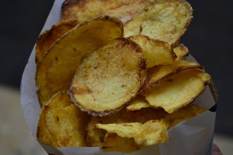 Patatine fritte gialle croccanti rotonde in primo piano bianco della borsa fotografia stock libera da diritti