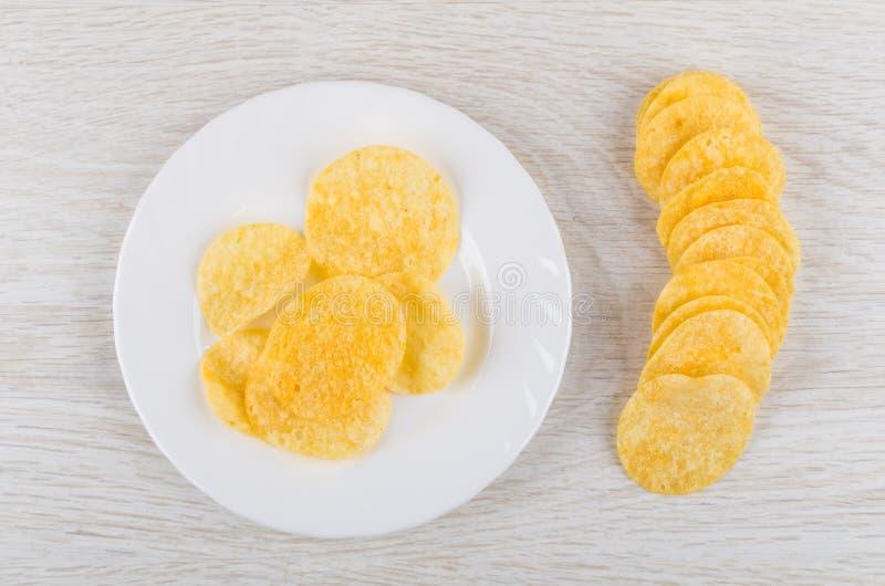 Patatine fritte in piatto bianco e sulla tavola di legno fotografie stock