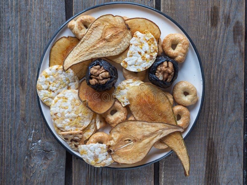 Patatine fritte utili dei cereali e dei frutti secchi, prugne con i dadi e biscotti del cereale su un piatto ceramico rimosso dal fotografie stock