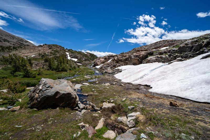 Patch of remaining snow along the 20 Lakes Basin hiking trail in Eastern Sierra Nevada Mountains of California on a sunny summer. Day stock photo