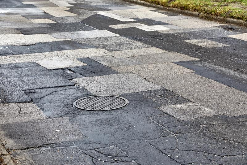 Patched broken road. Extremely bad quality road with many patches, potholes royalty free stock images