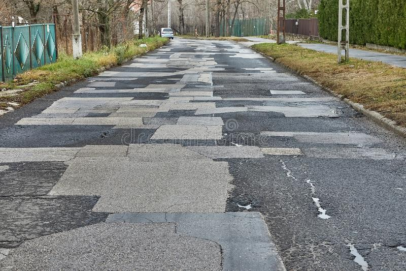 Patched broken road. Extremely bad quality road with many patches, potholes stock images