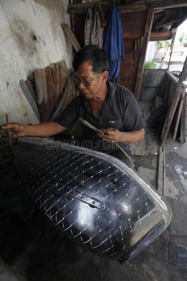 Patching tank. Technicians were patching a leaking tank of motorcycles in the city of Solo, Central Java, Indonesia royalty free stock photography