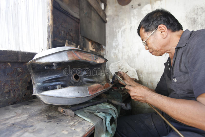 Patching tank. Technicians were patching a leaking tank of motorcycles in the city of Solo, Central Java, Indonesia royalty free stock photos