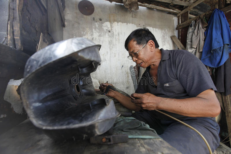 Patching tank. Technicians were patching a leaking tank of motorcycles in the city of Solo, Central Java, Indonesia stock photo