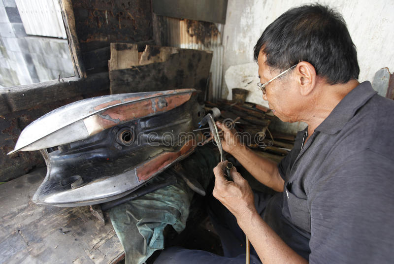 Patching tank. Technicians were patching a leaking tank of motorcycles in the city of Solo, Central Java, Indonesia royalty free stock photo