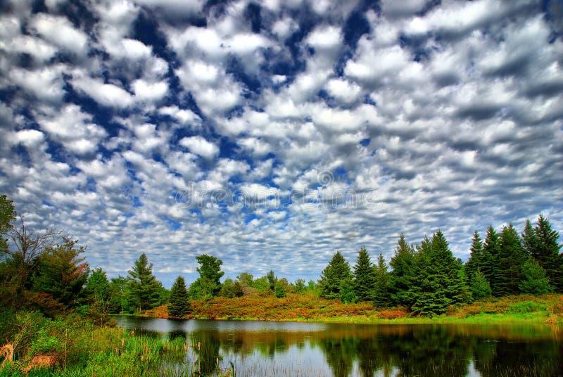 Patchwork-Himmel über Land-Teich lizenzfreies stockfoto