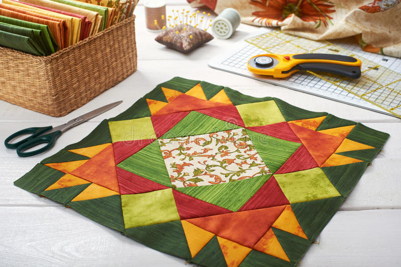 Patchwork orange-green block, quilting fabrics, sewing accessories royalty free stock photo