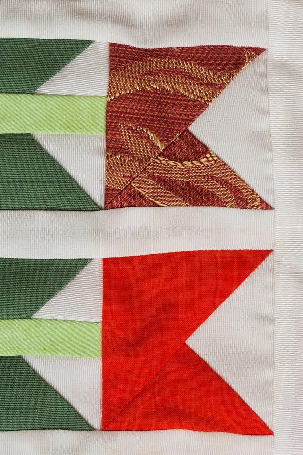 Patchwork som syr, modebegrepp - makro på det härliga täcket som sys från rester av kulöra torkdukar i matning av bestämt arkivfoto