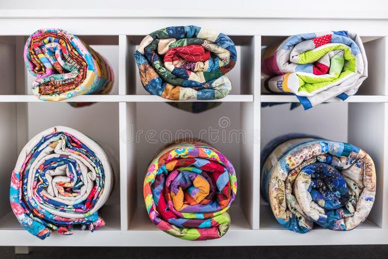 Patchwork, szący, pojęciu, dostosowywać i mody - jaskrawe skończone kołderki w studiu w sklepie lub, biel odkładają obrazy royalty free