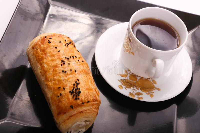 Tea with paté. Pate with cup of tea on modern black dish over white background royalty free stock photo