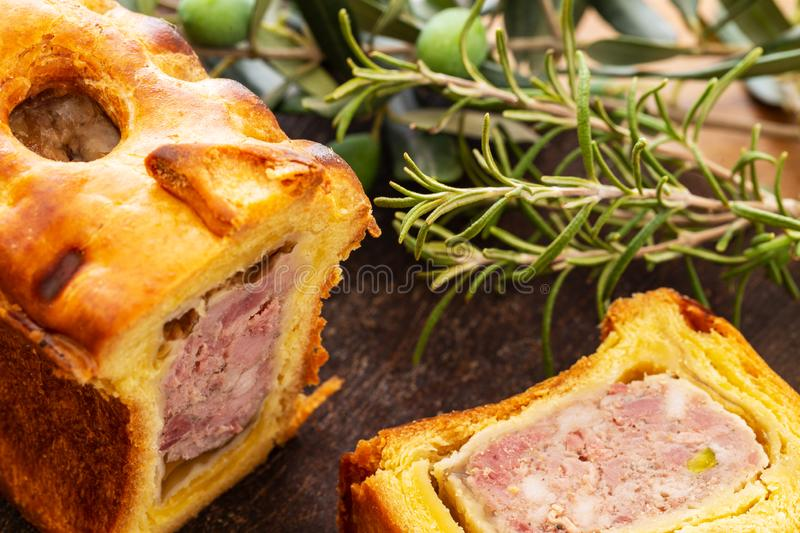 Pate en croute or pâté en croûte with rosemary twig and green olives on branch with leaves over a dark wooden cutting board and. Pate en croute or pâ royalty free stock photo