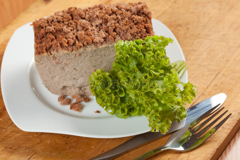 Pate. Venison pate on a plate decorated with salad royalty free stock photography