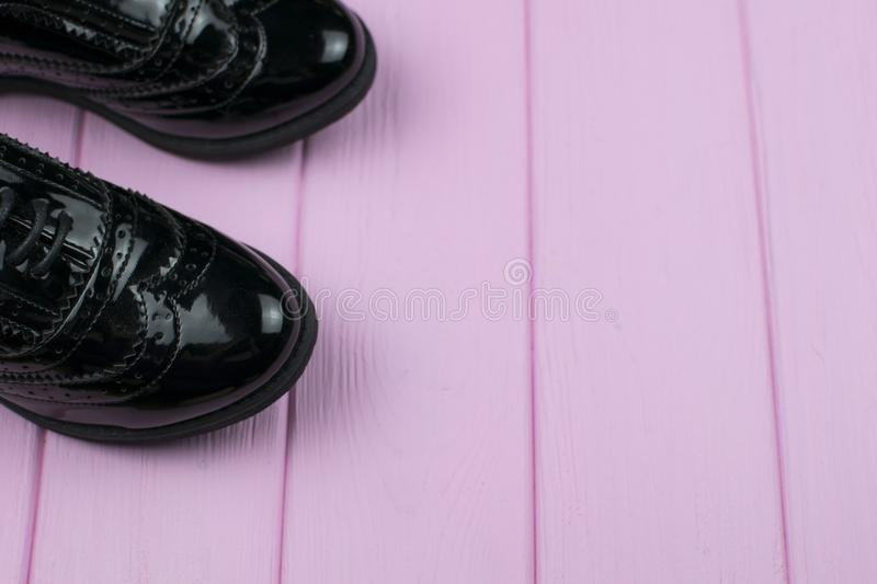 Patent leather black shoes. With laces on a wooden painted surface royalty free stock photography
