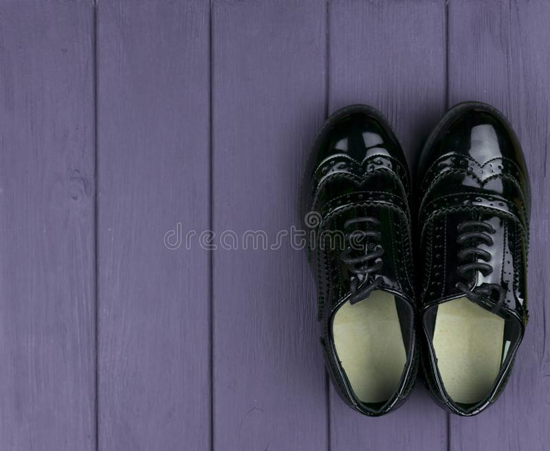 Patent leather black shoes. With laces on a purple wooden surface stock photography