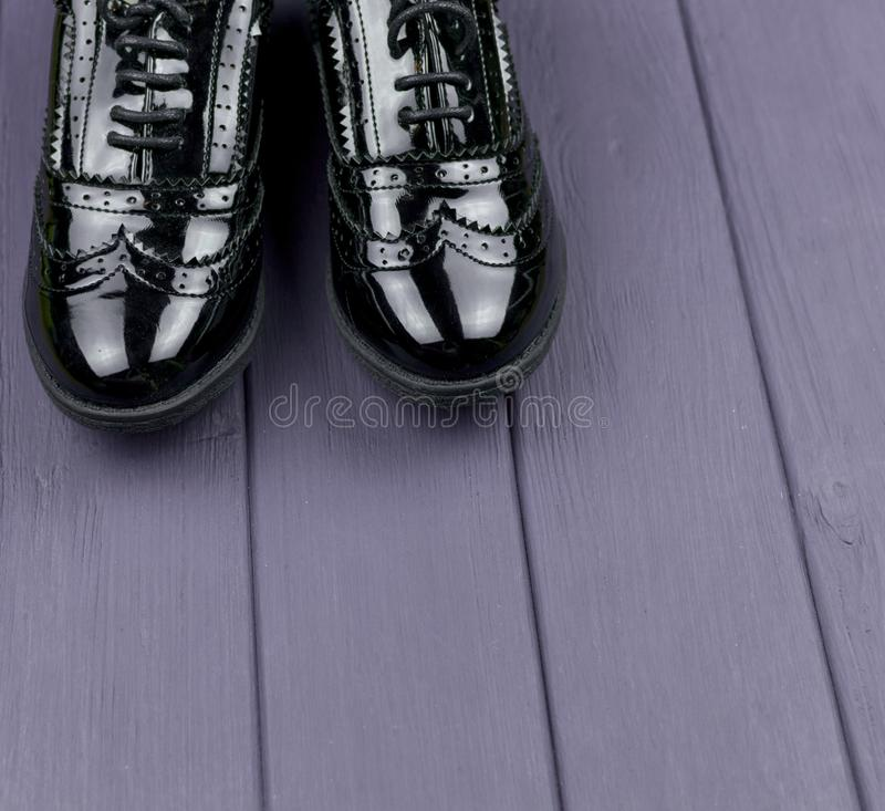 Patent leather black shoes. With laces on a purple wooden surface stock photos