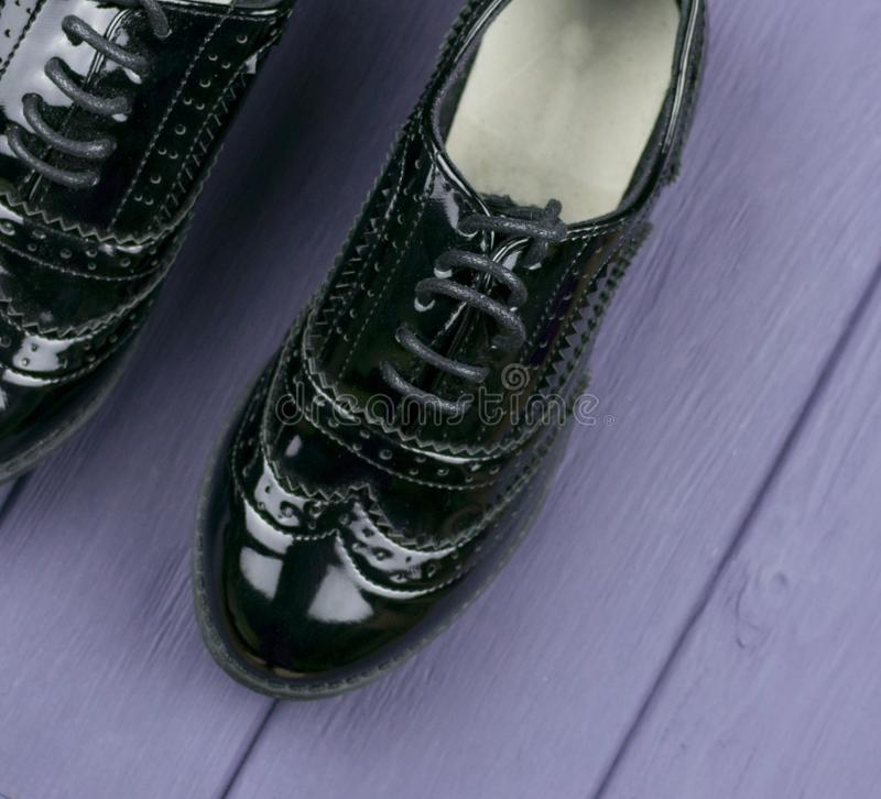 Patent leather black shoes. With lacing on a lilac wooden surface stock photo