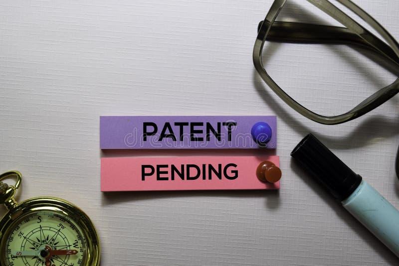 Patente hasta que finalice el texto en las notas pegajosas aisladas en el escritorio de oficina fotos de archivo