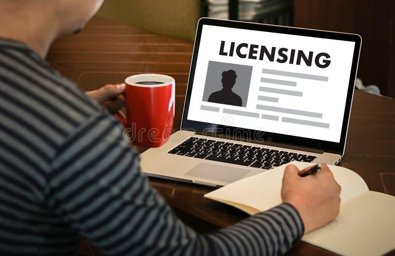 Patente la mano del hombre de negocios de la AUTORIZACIÓN del contrato de licencia que trabaja o fotografía de archivo