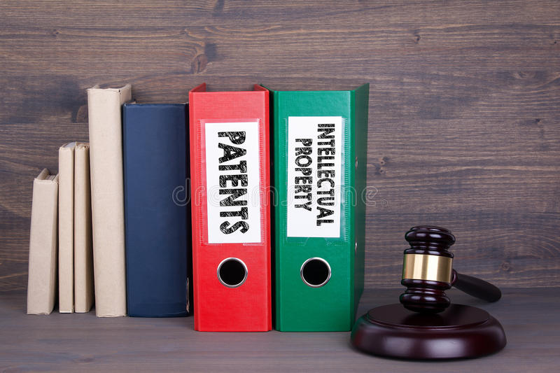 Patents and Intellectual Property. Wooden gavel and books in background. Law and justice concept.  stock photo