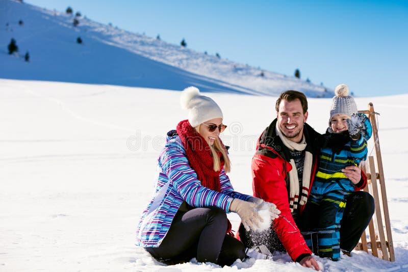 Paternidad, moda, estación y concepto de la gente - familia feliz con el niño en el trineo que camina en invierno al aire libre fotografía de archivo
