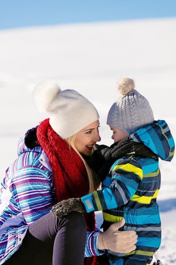 Paternidad, moda, estación y concepto de la gente - familia feliz con el niño en el trineo que camina en invierno al aire libre imagen de archivo libre de regalías