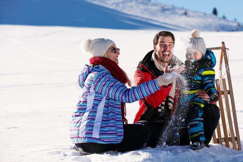 Paternidad, moda, estación y concepto de la gente - familia feliz con el niño en el trineo que camina en invierno al aire libre foto de archivo