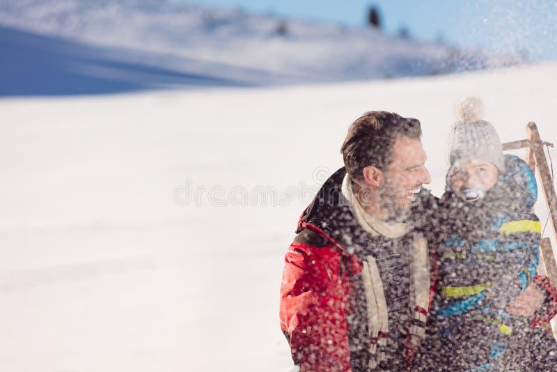 Paternidad, moda, estación y concepto de la gente - familia feliz con el niño en el trineo que camina en invierno al aire libre imágenes de archivo libres de regalías