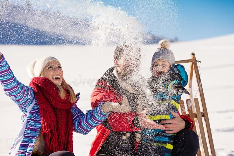 Paternidad, moda, estación y concepto de la gente - familia feliz con el niño en el trineo que camina en invierno al aire libre imagen de archivo