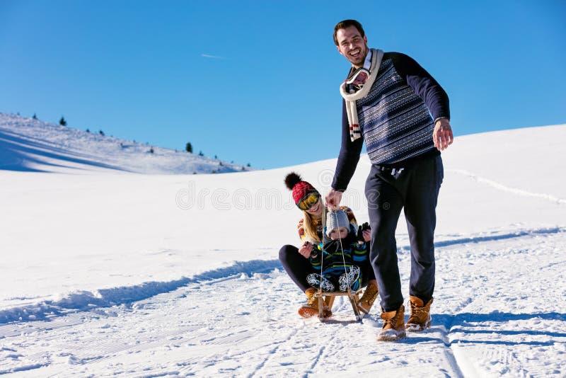 Paternidad, moda, estación y concepto de la gente - familia feliz con el niño en el trineo que camina en invierno al aire libre fotos de archivo