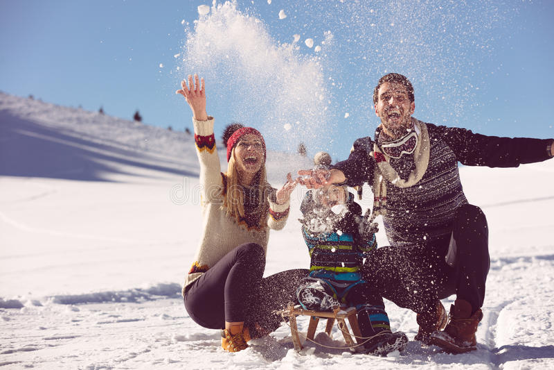 Paternidad, moda, estación y concepto de la gente - familia feliz con el niño en el trineo que camina en invierno al aire libre imagenes de archivo