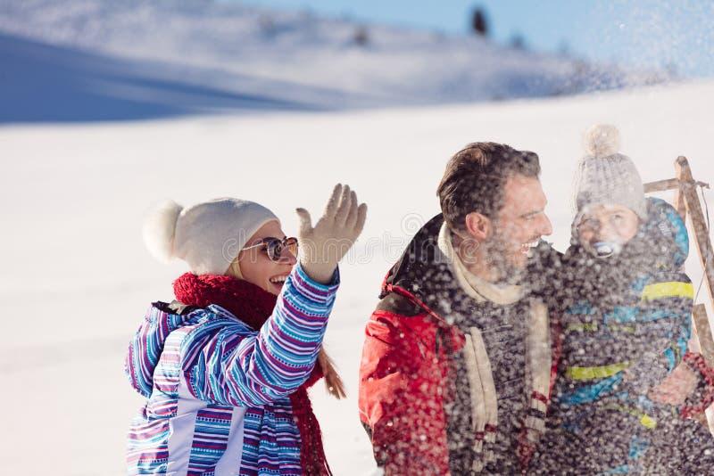Paternità, modo, stagione e concetto della gente - famiglia felice con il bambino sulla slitta che cammina nell'inverno all'apert immagini stock