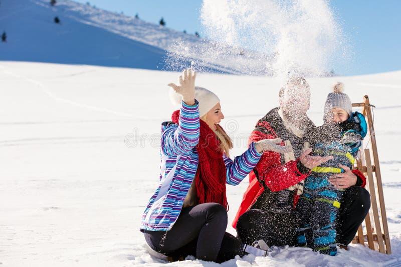 Paternità, modo, stagione e concetto della gente - famiglia felice con il bambino sulla slitta che cammina nell'inverno all'apert fotografie stock